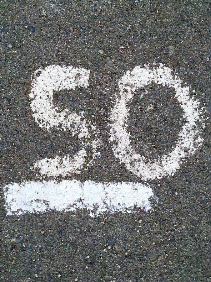 På numret är 50 skriftliga med vit målarfärg på den gråa asfalten royaltyfri fotografi