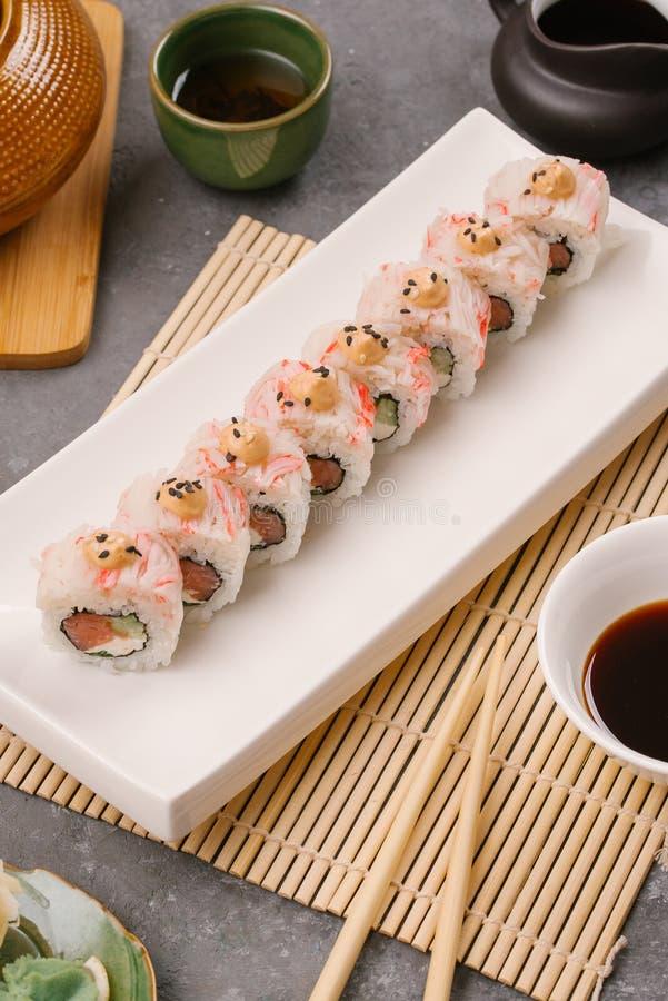 På plattan vit, fodrat med läckra rullar, är sushi, rött som är svart, Philadelphia sesam arkivfoton