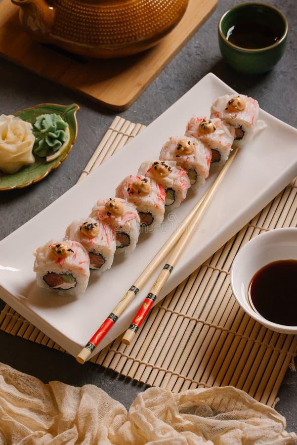 På plattan vit, fodrat med läckra rullar, är sushi, rött som är svart, Philadelphia sesam arkivfoto