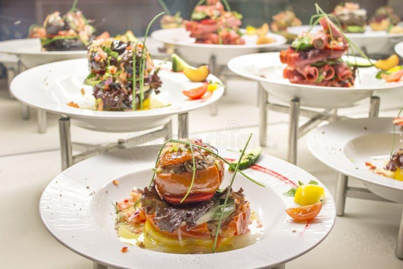 På plattorna som ut läggas många grönsaker och kött, är de alla välfyllda med köttfärs, peppar, tomater, bacon fotografering för bildbyråer