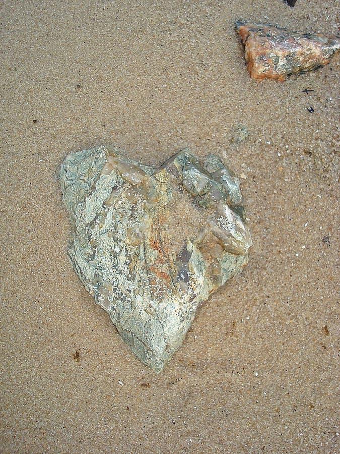 På sandlögnerna en sten i formen av hjärtan royaltyfri fotografi