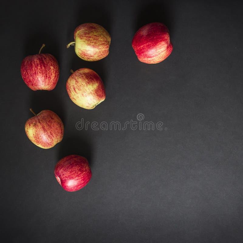 På sikt för ram för äpplen för bakgrund för mörk svart en röd gul från lekmanna- fyrkant för ovannämnd lägenhet royaltyfri bild