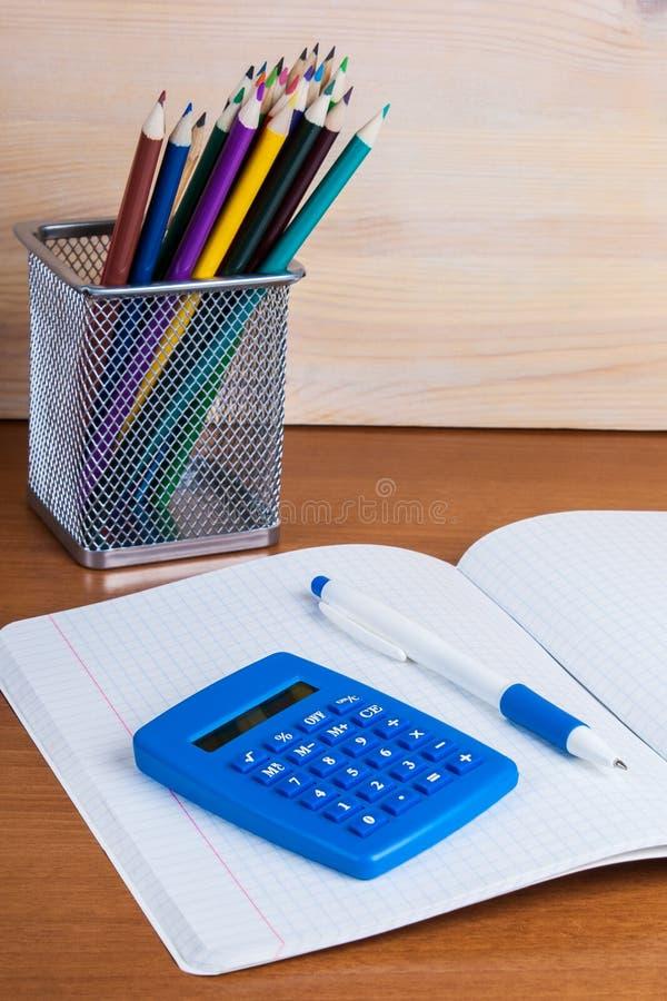 På skrivboken in i en liggande blå räknemaskin och penna för cell fotografering för bildbyråer