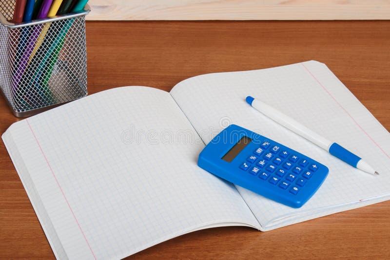 På skrivboken in i en liggande blå räknemaskin och penna för cell arkivfoton