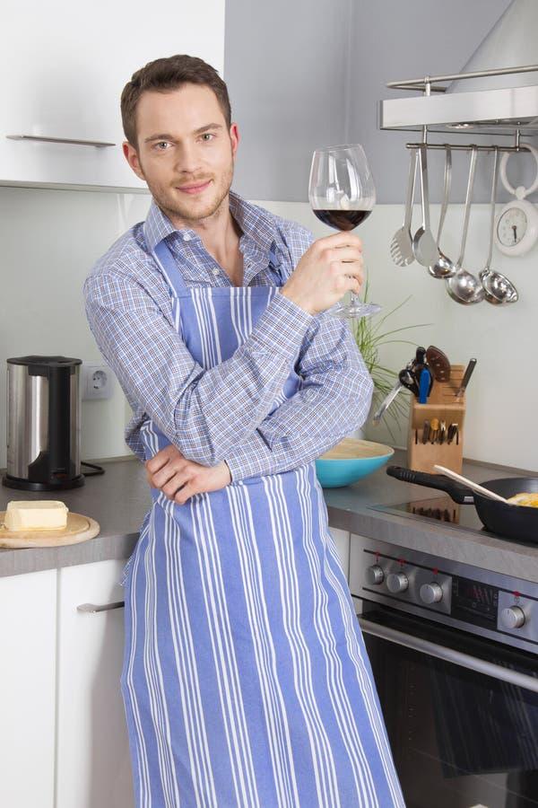 På slutet av arbete: enkel man som dricker exponeringsglas av vin i satsen arkivbild