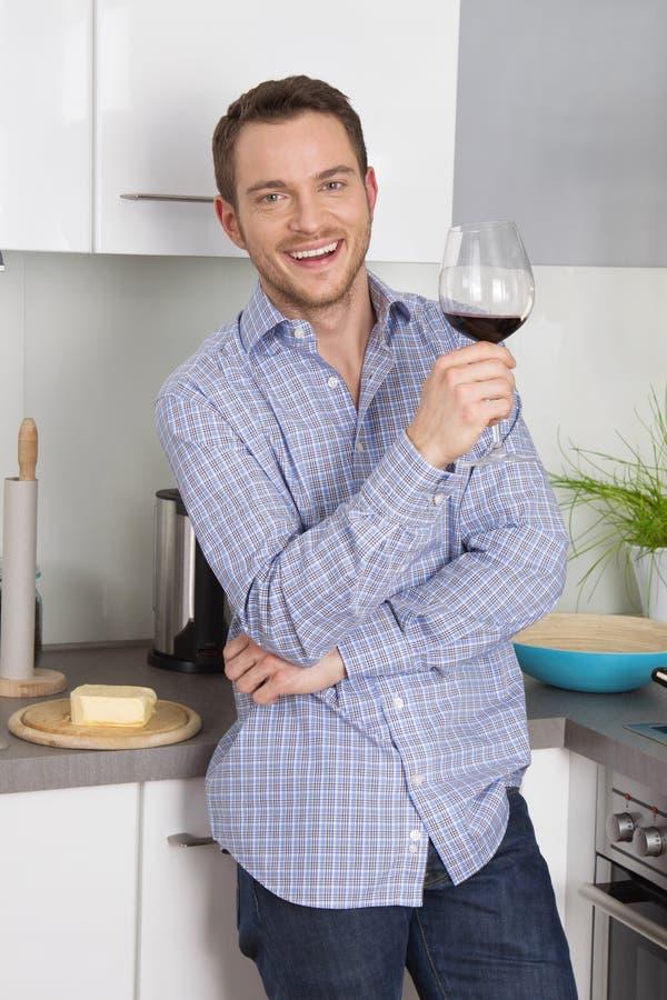 På slutet av arbete: enkel man som dricker exponeringsglas av vin i satsen royaltyfria foton