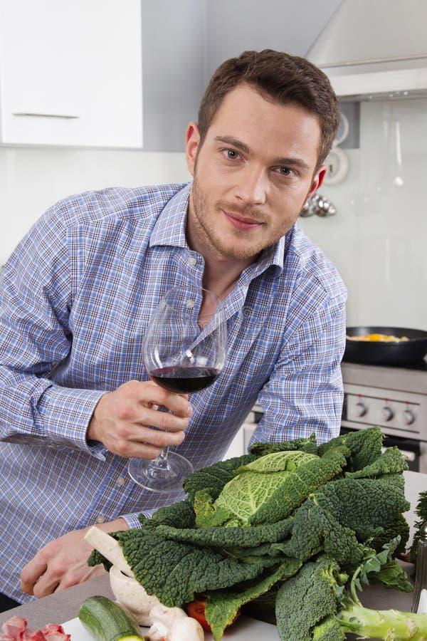 På slutet av arbete: enkel man som dricker exponeringsglas av vin i satsen royaltyfria bilder