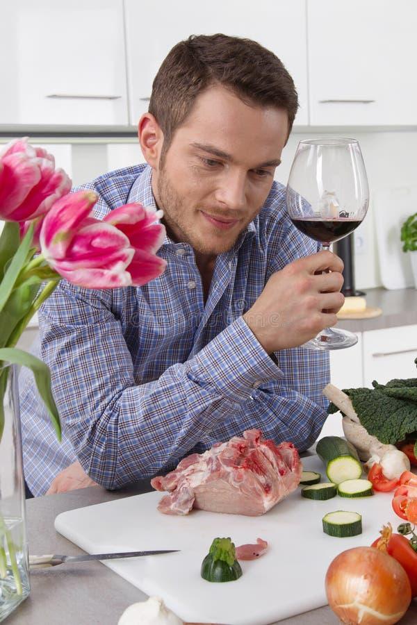 På slutet av arbete: enkel man som dricker exponeringsglas av vin i satsen royaltyfri bild