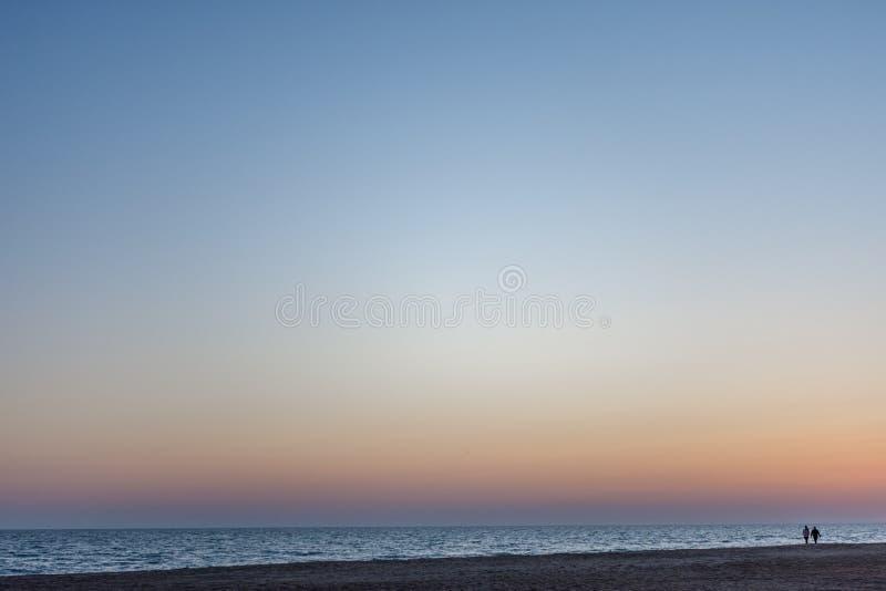 På solnedgången ett par av vänner som promenerar havet arkivfoton