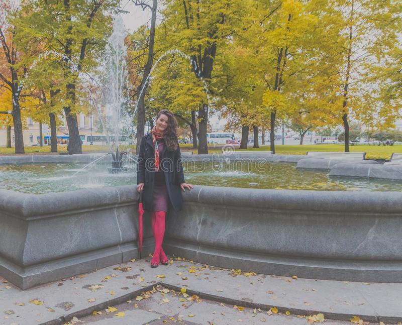 På springbrunnen på en molnig dag med en paraplyflicka arkivfoto