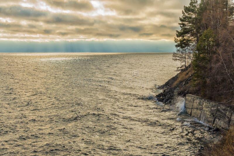 På stranden av sjön Baikal i november Vackra himlen över sjön Vågen går sönder på klipporna royaltyfri foto