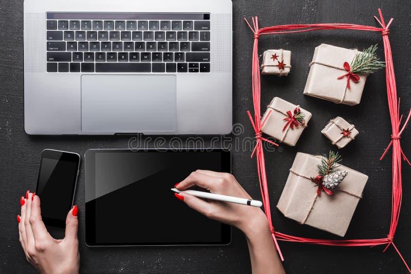 På svart bakgrund, många gåvor och teknik På minnestavlan önskar händer för dam` ett s fotografering för bildbyråer