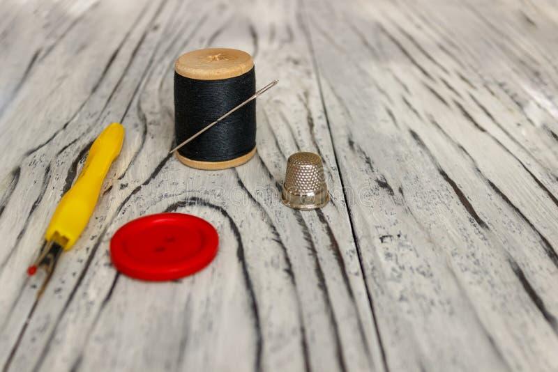 På svart vadderat tyg applicerar närbilden, sax och tråden med en visare royaltyfri foto