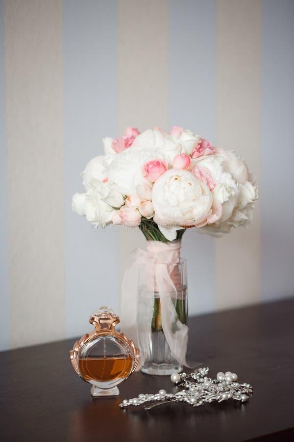 På tabellen är en bukett av blommor i en vas, en doft och en hårspänne arkivbilder