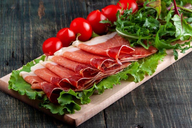 På tabellen är en träskärbräda med skivade jamon, tomater och örter royaltyfri fotografi