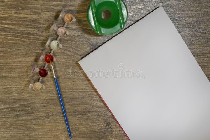 På tabellen är en uppsättning för att dra: en borste, gouache och ett vitt ark av papper På en röd målarfärg för borste arkivbild