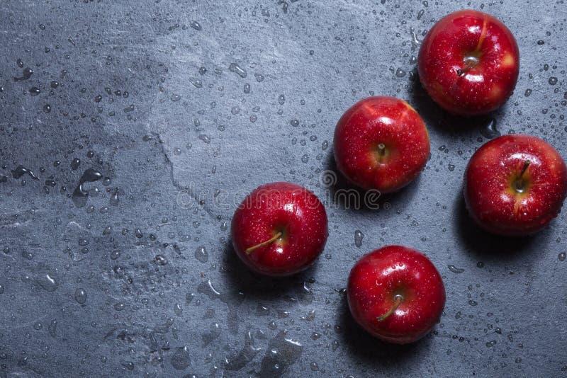 På tabellen är tre röda äpplen royaltyfri bild