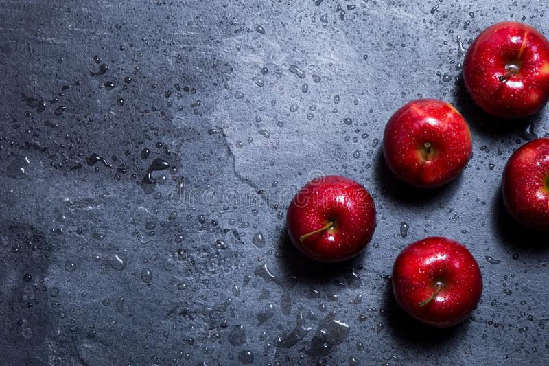 På tabellen är tre röda äpplen arkivbilder