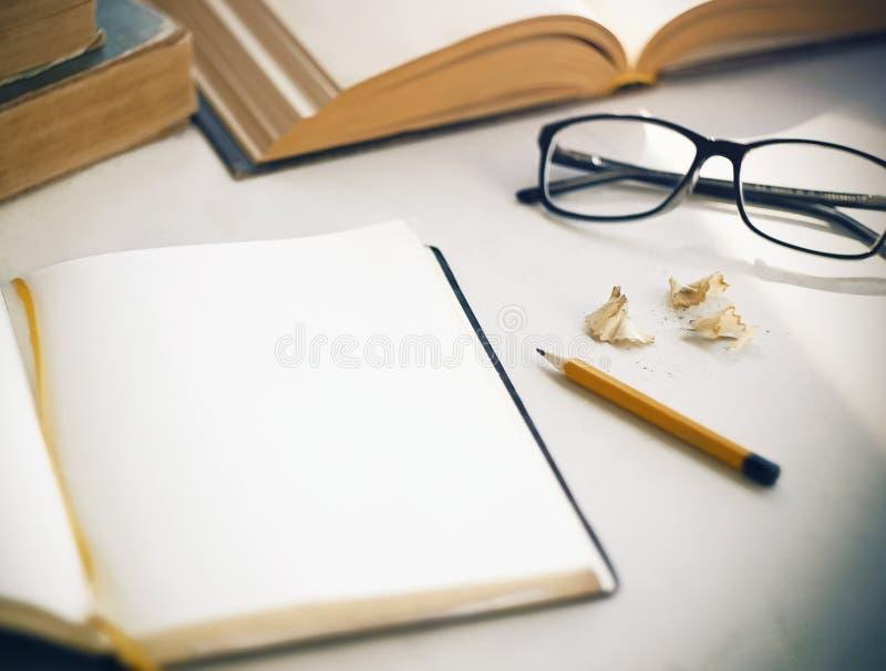 På tabellen finns det gamla böcker, en öppen dagbok, shavings, en gul blyertspenna och exponeringsglas royaltyfri foto