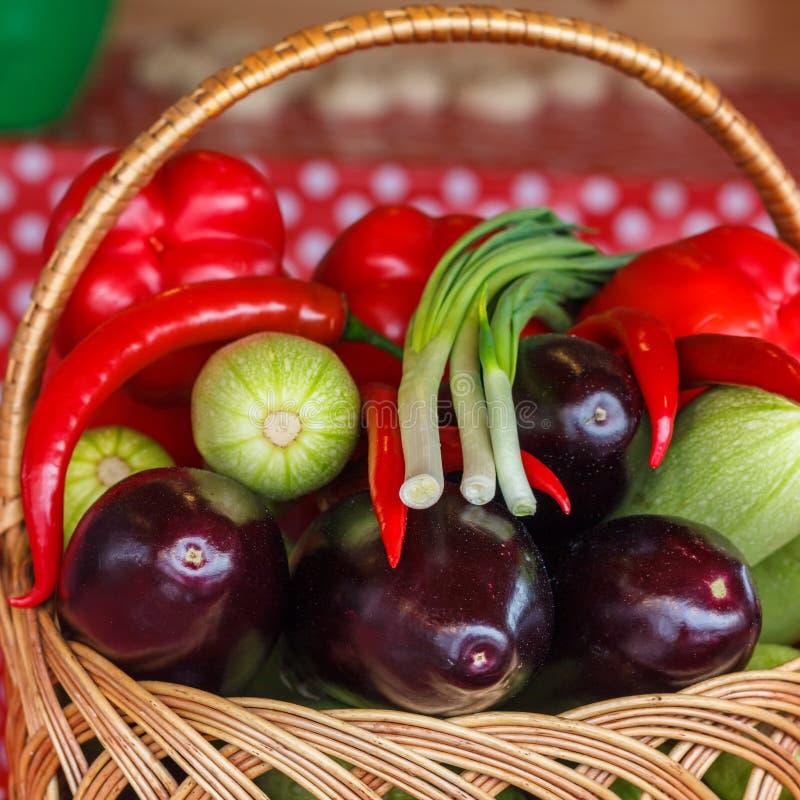 På tabellen i korgen lägga grönsaker: aubergine zucchini, röd peppar, bitter peppar arkivbilder