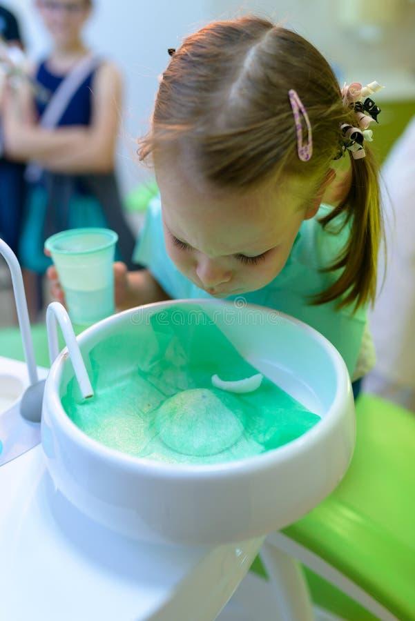 På tandläkaren tand- tålmodiga spottar flickan vatten efter behandling royaltyfri foto