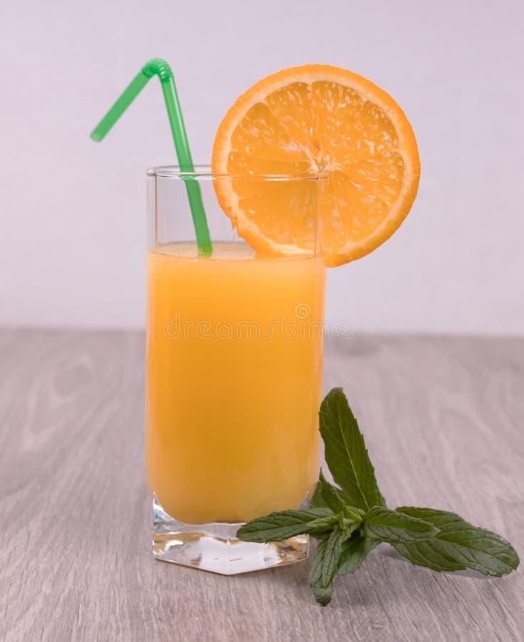 P? tr?yttersidan av fruktsaftbunten med ett sugr?r som dekoreras med en n?rliggande orange skiva, och mintkaramellkvist arkivfoton