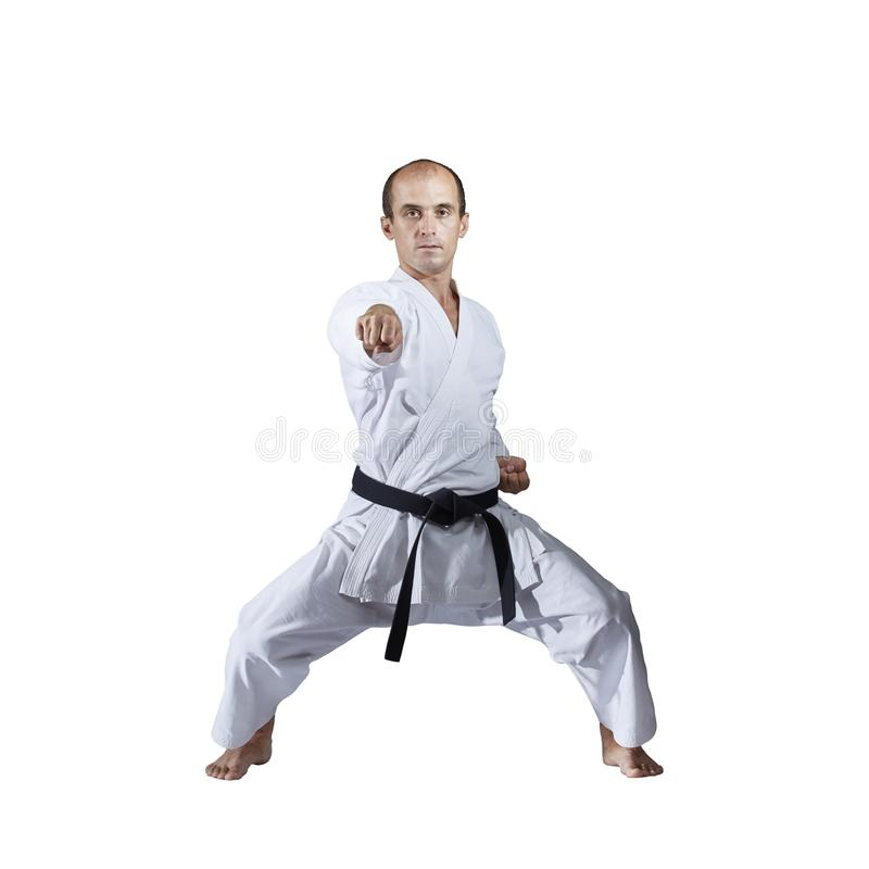 På vit bakgrund utbildar den vuxna aktiva idrottsman nen formella karateövningar arkivfoton