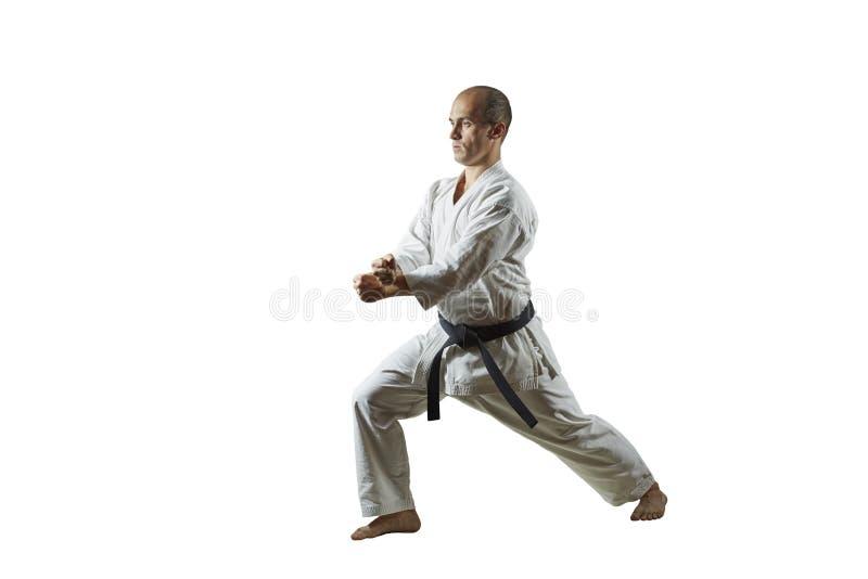 På vit isolerad bakgrund utför idrottsman nen formella karateövningar arkivbild