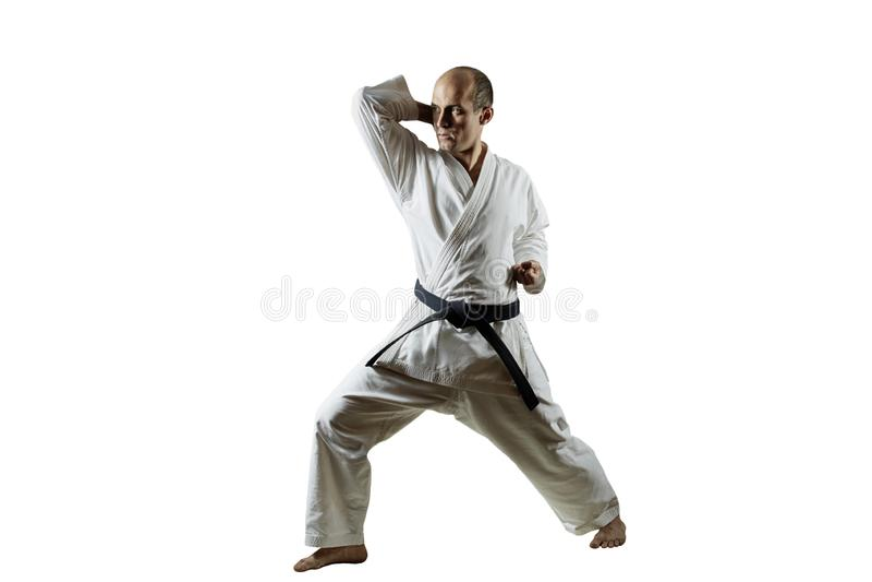 På vit isolerad bakgrund utför idrottsman nen formella karateövningar arkivbilder