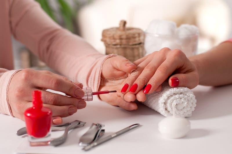 på white Röd härlig wiith för handen för kvinna` s spikar i brunnsorten fotografering för bildbyråer