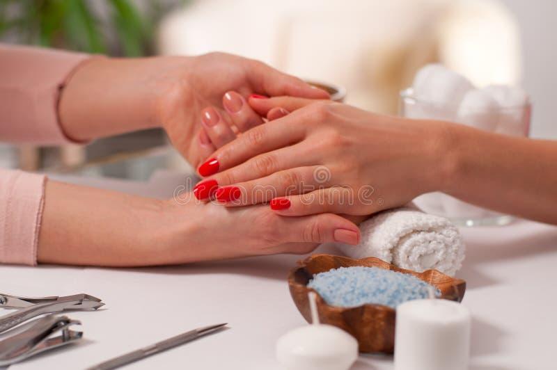 på white Röd härlig wiith för handen för kvinna` s spikar i brunnsorten royaltyfria bilder