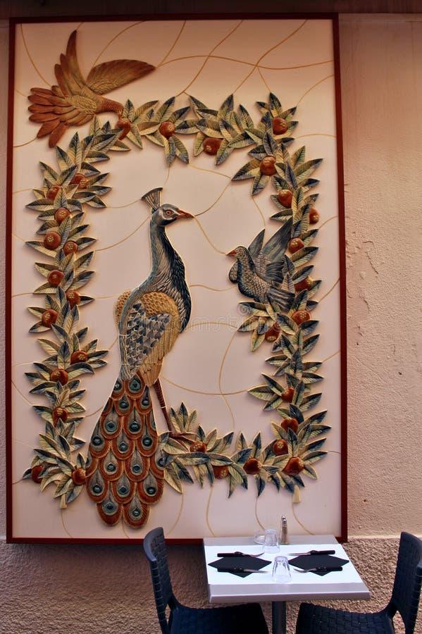 Påfågel med den keramiska väggen för duvor ovanför en restaurangtabell arkivfoto