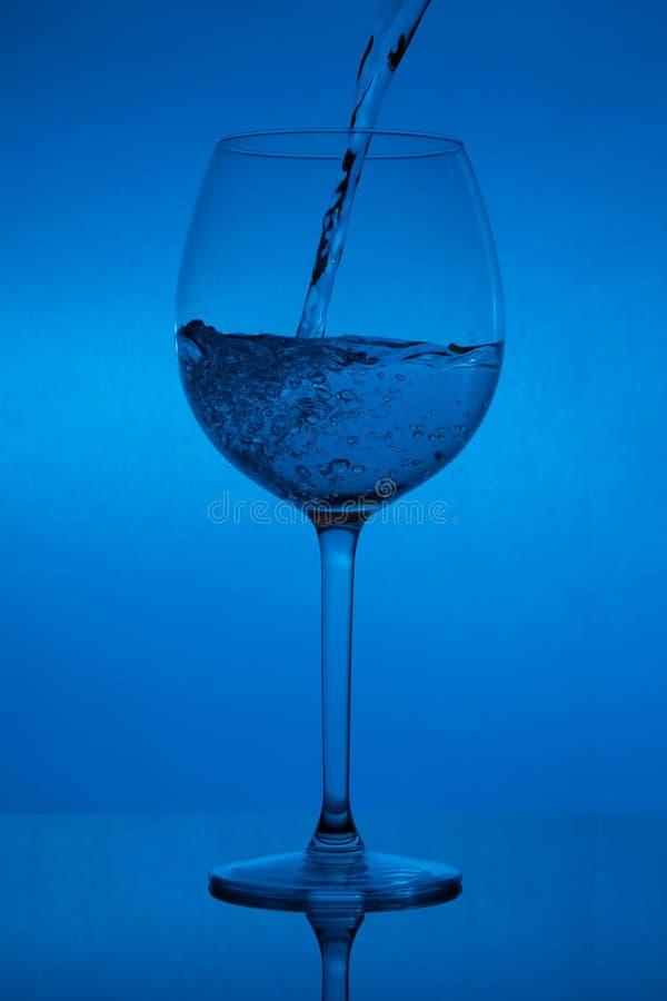 Påfyllning av exponeringsglaset, hällande vinglas på blå bakgrund arkivfoto
