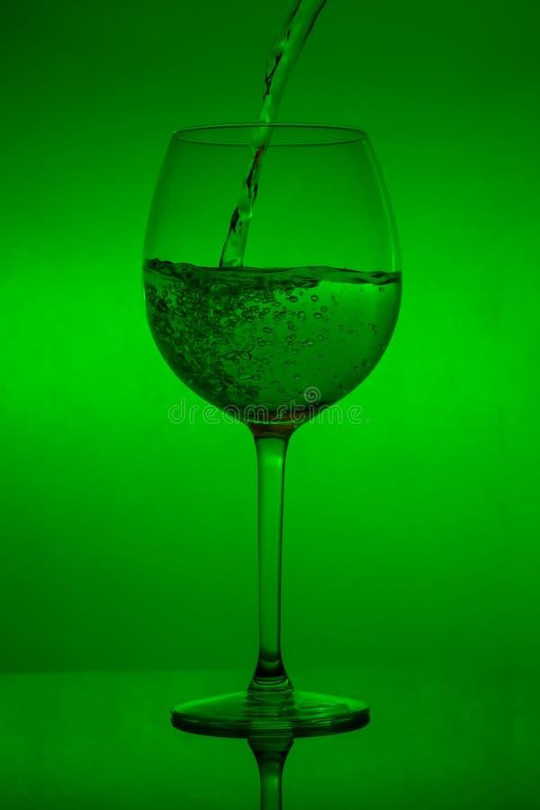 Påfyllning av exponeringsglaset, hällande vinglas på grön bakgrund royaltyfri fotografi