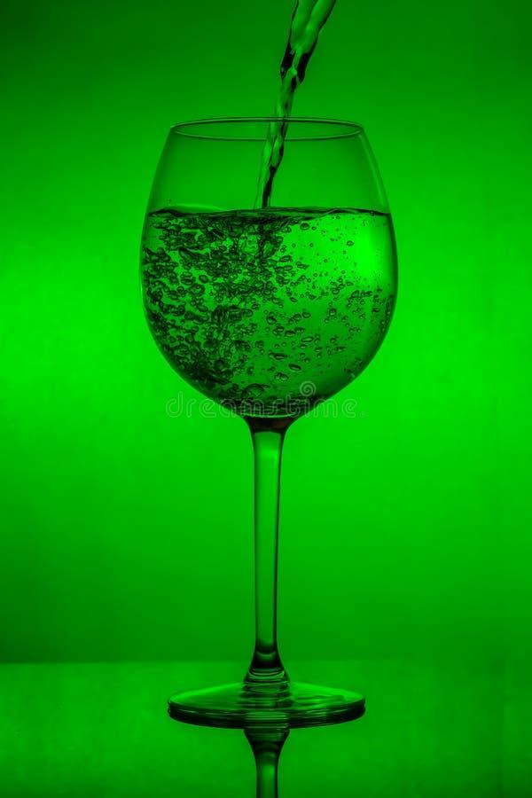 Påfyllning av exponeringsglaset, hällande vinglas på grön bakgrund fotografering för bildbyråer