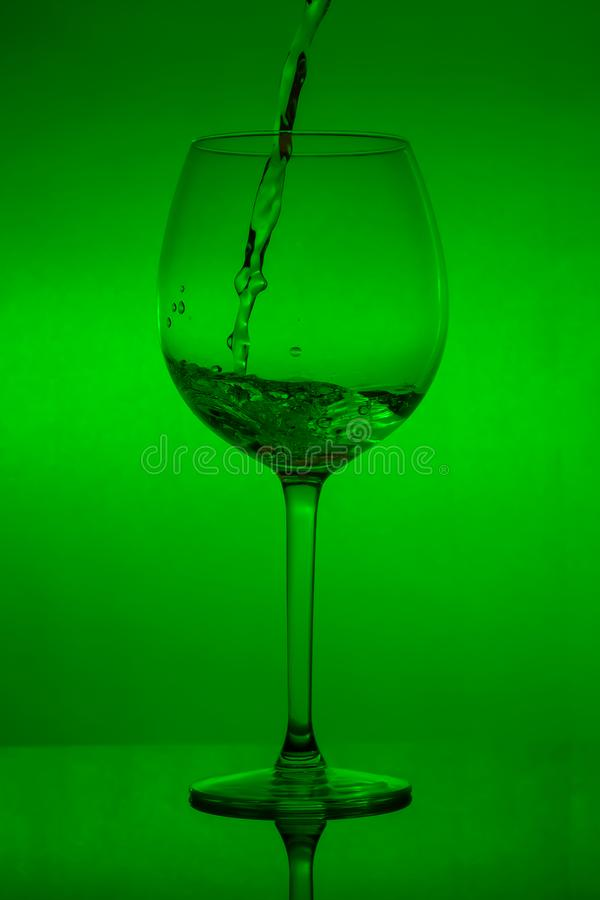 Påfyllning av exponeringsglaset, hällande vinglas på grön bakgrund arkivbild