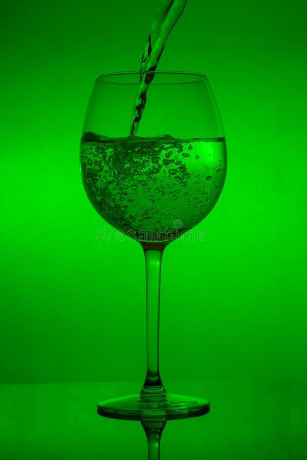 Påfyllning av exponeringsglaset, hällande vinglas på grön bakgrund royaltyfri foto