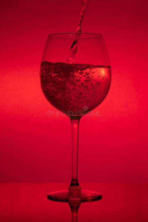 Påfyllning av exponeringsglaset, hällande vinglas på röd bakgrund royaltyfri foto