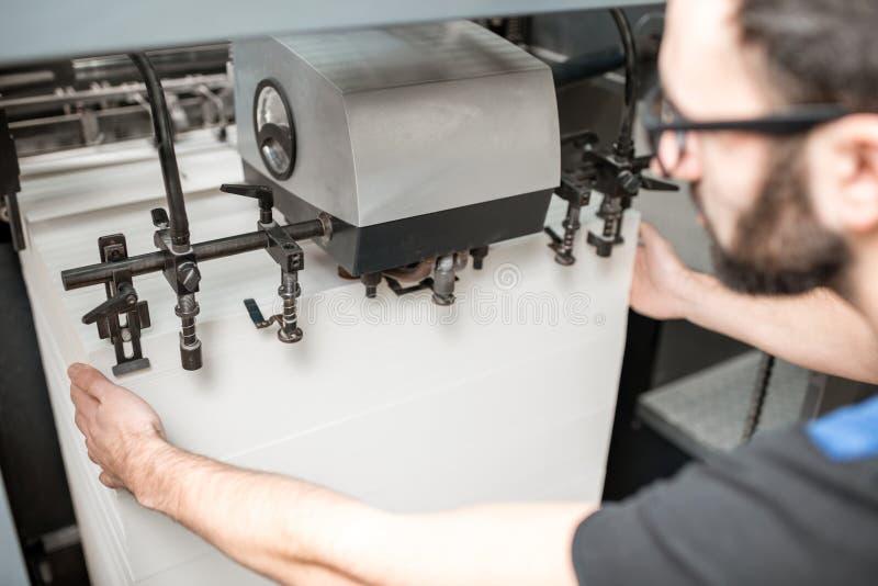 Påfyllning ett papper in i printingmaskinen arkivfoton