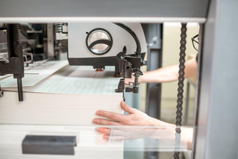 Påfyllning ett papper in i printingmaskinen royaltyfri foto