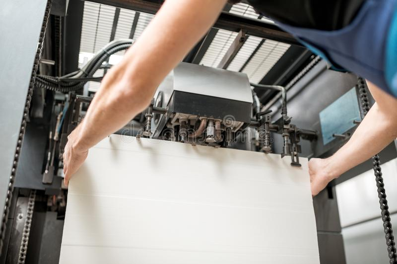 Påfyllning ett papper in i printingmaskinen royaltyfri bild