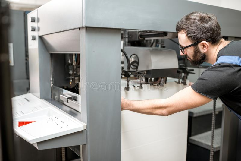Påfyllning ett papper in i printingmaskinen royaltyfri fotografi