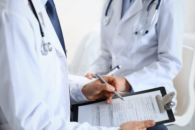 Påfyllning för två medicinsk form för okänd doktorer på skrivplattan, precis handcloseup Läkare som frågar fråga till patienten e royaltyfria foton