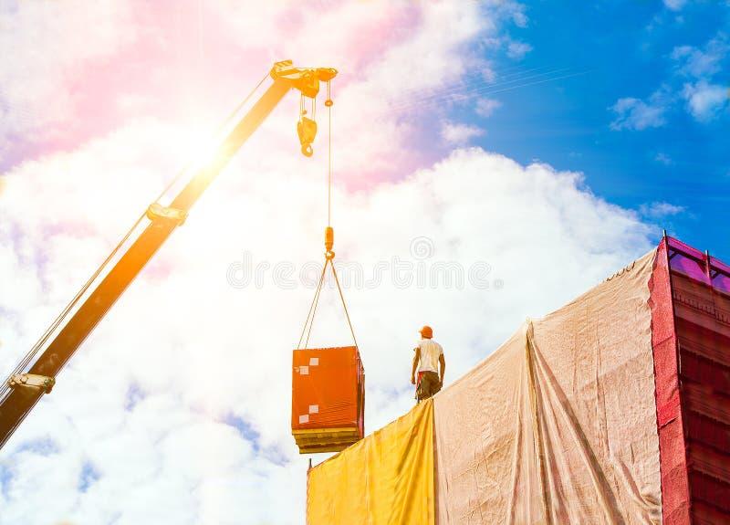 Påfyllning på kroken av kranen En manbyggmästare i en hjälm tar en påfyllning på taket av byggnaden royaltyfria bilder