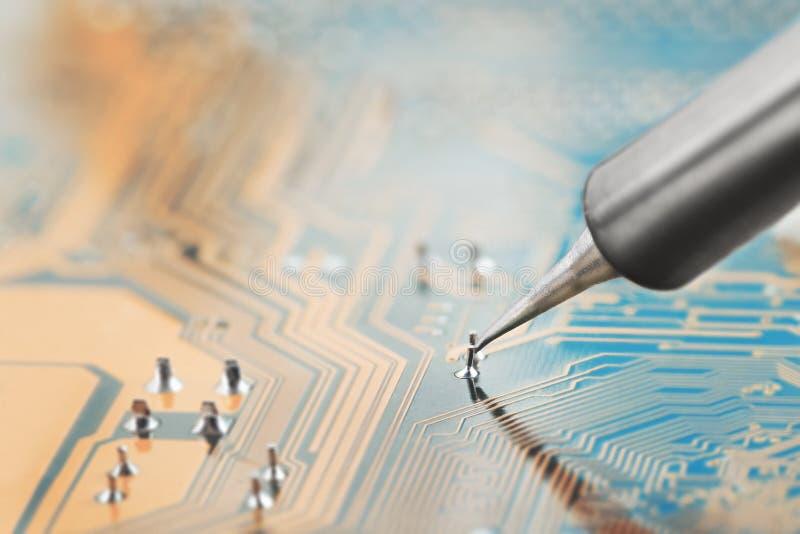 Pågående arbete Löda av brädet för elektronisk strömkrets med elektroniska delar lödande station Teknikerreparationsströmkrets bo royaltyfri foto