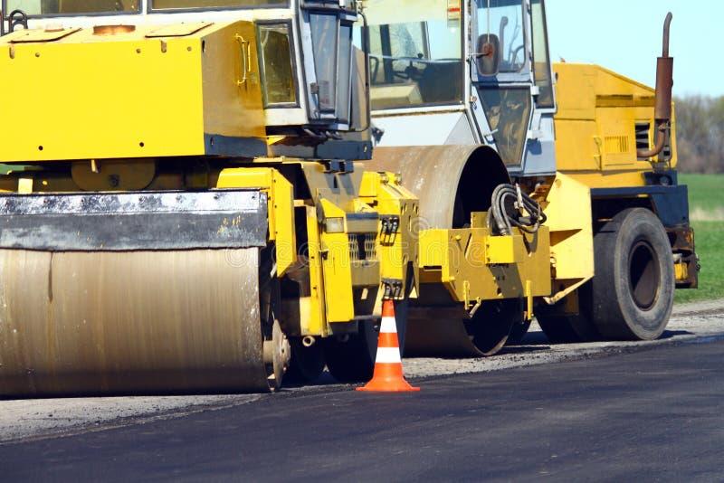 Pågående vägkonstruktion och att asfaltera vägen med modern utrustning royaltyfri foto