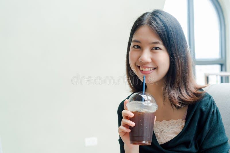 Pålagd asiatisk härlig kvinna en svart skjorta, ställning som dricker kallt kaffe i handen med nöje royaltyfri foto