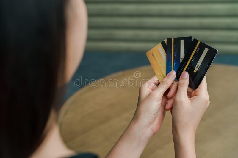 Pålagd asiatisk härlig kvinna för Closeup en svart skjorta och ställning mot träpelaren i mitt av huset Anv?nd en b?rbar dator arkivfoton