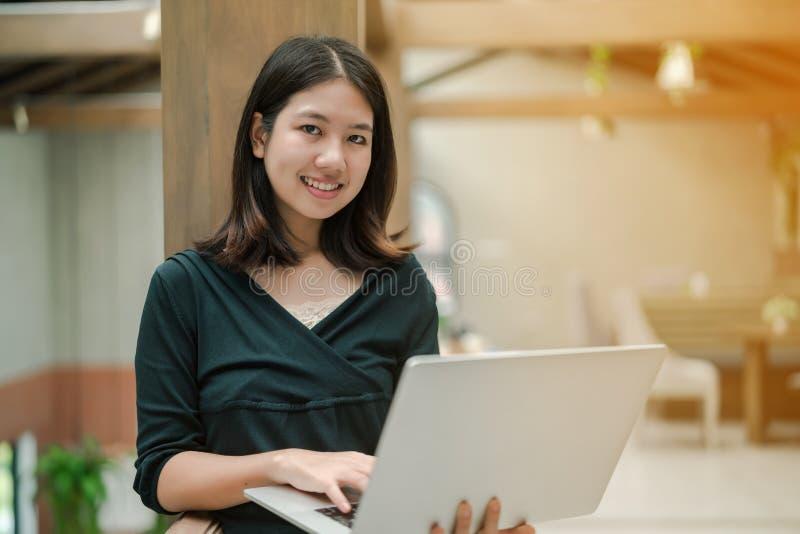 Pålagd asiatisk härlig kvinna för Closeup en svart skjorta och ställning mot träpelaren i mitt av huset Anv?nd en b?rbar dator royaltyfri bild