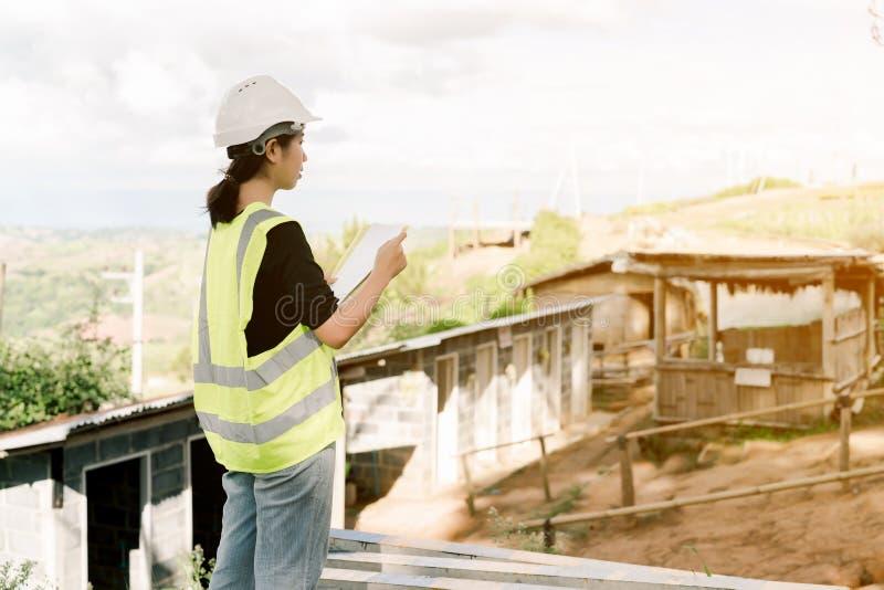 Pålagd asiatisk kvinnlig tekniker en vit säkerhetshatt som bär en grön säkerhetsskjortaställning för konstruktionskontroll i kons fotografering för bildbyråer